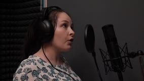 Portret van jong aantrekkelijk meisje met blauwe ogen die lied zingen Vrouw die in muziekstudio repeteren Controleapparaat stock videobeelden