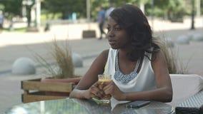 Portret van jong Afrikaans vrouw nippend jus d'orange en het dromen, terwijl het zitten in koffie stock videobeelden