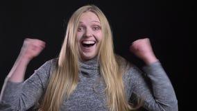 Portret van jong blonde recht-haired model die extreem schok en geluk tonen in camera op zwarte achtergrond stock footage
