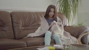Portret van jong die meisje in een deken wordt verpakt die haar neus in een servetzitting thuis blazen op de leerbank Het meisje stock videobeelden