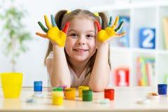 Portret van jong geitjemeisje met gezicht en geschilderde handen Stock Foto's