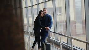 Portret van jong gelukkig paar die met bagage elkaar in luchthaven bekijken stock video