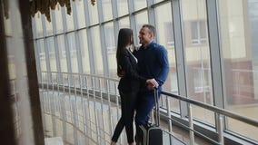 Portret van jong gelukkig paar die met bagage elkaar in luchthaven bekijken stock footage
