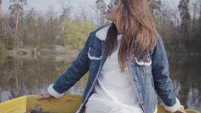 Portret van jong glamourbrunette in modieus glazen en jeansjasje die in de camera kijken Mooi landschap  stock footage