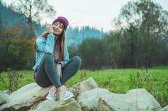 Portret van jong hipstermeisje die van een verbazende mening van bergen genieten, vrij vrouwelijke reiziger, die op grote stenen  royalty-vrije stock afbeeldingen