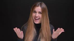 Portret van jong Kaukasisch langharig blondemeisje die vermaak tonen in camera op zwarte achtergrond stock video