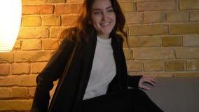 Portret van jong Kaukasisch meisje met golvende haarzitting op bank en het letten van op TV met groot enthousiasme op comfortabel stock videobeelden