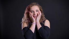 Portret van jong Kaukasisch meisje met het roze haar letten op in camera met vermaak op zwarte achtergrond stock footage