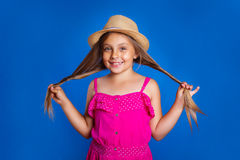Portret van jong leuk meisje in roze kleding en hoed op blauwe achtergrond De zomervakantie en reisconcept Stock Fotografie