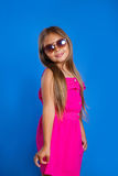 Portret van jong leuk meisje in roze kleding en hoed op blauwe achtergrond De zomervakantie en reisconcept Royalty-vrije Stock Foto's