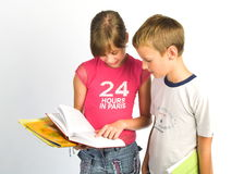 Portret van jong meisje en jongenslezingsboek Stock Foto's