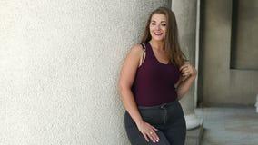 Portret van jong meisje met bovenmatig gewicht in het park op een grijze muurachtergrond stock videobeelden
