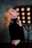 Portret van jong modieus mooi aantrekkelijk krullend meisje in zwarte sweater op het stadium stock fotografie