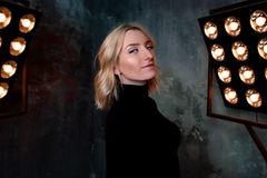 Portret van jong modieus mooi aantrekkelijk krullend meisje in zwarte sweater op het stadium stock foto's