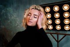 Portret van jong modieus mooi aantrekkelijk krullend meisje in zwarte sweater op het stadium stock afbeelding