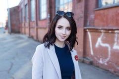 Portret van jong mooi glimlachend meisje met bruin haar in de stad royalty-vrije stock afbeelding