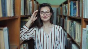 Portret van jong mooi meisje in bibliotheek Vrouwelijke student die onder partij van boeken tussen shelfs bestuderen stock videobeelden