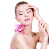 Portret van jong mooi meisje met bloem dichtbij het gezicht Royalty-vrije Stock Foto's