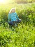 Portret van jong mooi meisje op een grasrijk gebied bij zonsondergang Royalty-vrije Stock Afbeeldingen