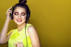 Portret van jong mooi model met kleurrijk artistiek samenstelling en updohaar die aan de muziek in hoofdtelefoons en het glimlach Royalty-vrije Stock Foto's