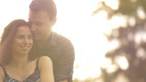 Portret van jong paar in liefde koesteren die zijnd gelukkige in openlucht zonsondergang lachen stock videobeelden