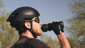 Portret van jong professioneel fietser drinkwater vóór zijn opleidingssessie Het cirkelen concept stock video