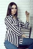 Portret van jong schitterend donker-haired model die jeans, gestreept overhemd met zakken en zwarte nauwsluitende halsketting dra Stock Afbeeldingen