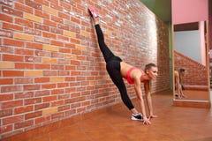 Portret van jong sportief meisje die uitrekkende oefening doen Stock Foto
