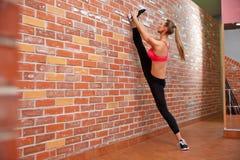 Portret van jong sportief meisje die uitrekkende oefening doen Stock Afbeelding