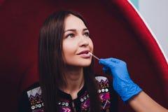 Portret van jong vrouw het bezoeken tandartsbureau voor tanden die met photopolymer witten stock foto