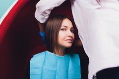 Portret van jong vrouw het bezoeken tandartsbureau voor tanden die met photopolymer witten royalty-vrije stock afbeelding