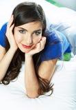 Portret van jong vrouwelijk model die in bed liggen Stock Afbeeldingen