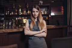 Portret van jong vrouwelijk model met eerlijk haar die haar ellebogen bij bar het tegen bekijken camera in uitstekend restaurant  stock afbeelding