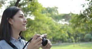 Portret van jonge aantrekkelijke Aziatische vrouwenfotograaf die foto's in een de zomerpark nemen stock videobeelden