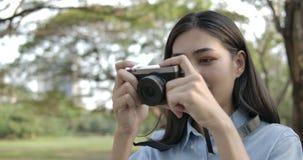 Portret van jonge aantrekkelijke Aziatische vrouwenfotograaf die foto's in een de zomerpark nemen stock video