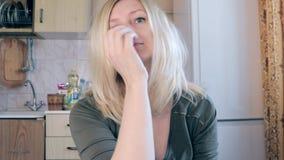 Portret van jonge aantrekkelijke blonde vrouw met blauwe ogen, seksuele huisvrouwenzitting in keuken en wat betreft en schuddend stock videobeelden