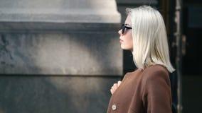 Portret van jonge aantrekkelijke blondevrouw in de herfststad Het meisje heeft modieus kijken, zonnebril en neus het doordringen  stock footage