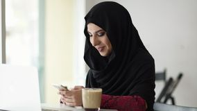 Portret van jonge aantrekkelijke glimlachende moslimvrouw in hijabzitting in de koffie en het typen van een bericht op haar mobie stock footage