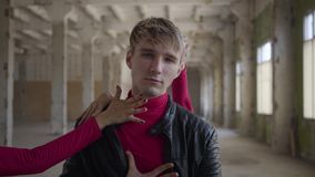 Portret van jonge aantrekkelijke kerel die met vrouwelijke handen geraakt wordt die prestaties maken of video schieten stock videobeelden