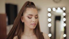 Portret van jonge aantrekkelijke vrouw met mooie make-up in de salon van de schoonheidsstudio Het gelijk maken maakt omhoog Achte stock footage