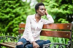 Portret van jonge Afrikaanse Amerikaanse vrouw met de zitting van het afrokapsel op de houten bank openlucht royalty-vrije stock afbeelding