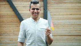 Portret van jonge Arabier die Duitse vlag golven en in openlucht in stadsstraat glimlachen stock videobeelden