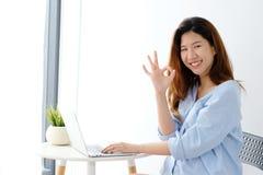 Portret van jonge Aziatische vrouw die het o.k. handteken en glimlachen w tonen royalty-vrije stock afbeelding