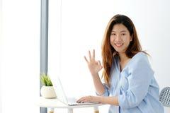 Portret van jonge Aziatische vrouw die o.k. handteken tonen en terwijl het werken met laptop computer, mensen met positief gebaar stock foto's