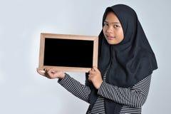 Portret van jonge Aziatische vrouw in het Islamitische bord van de headscarfholding Glimlachende Aziatische vrouw die Islamitisch royalty-vrije stock afbeelding