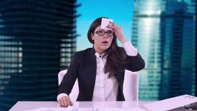 Portret van jonge bedrijfsvrouw in het bureau Het brunette in glazen verwijdert het geplakte stuk van document uit zijn voorhoofd stock footage