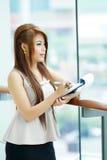 Portret van jonge bedrijfsvrouw status dichtbij venster in modern Stock Afbeelding