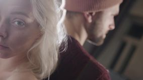 Portret van jonge blauwe eyed blondevrouw status dicht bij de gebaarde mens in hoed stock footage