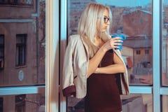 Portret van jonge blonde bedrijfsvrouw met kop thee dichtbij Stock Foto