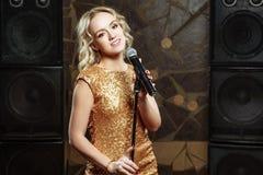 Portret van jonge blondevrouw met microfoon op donkere achtergrond stock foto's